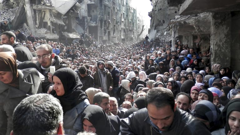 Residents of the besieged Palestinian camp of Yarmouk line up to receive food supplies from a UN agency in Damascus, Syria.