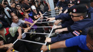 Thai pro-democracy protesters confront with riot police during a gathering marking the fourth anniversary of the military takeover in Bangkok on Tuesday.