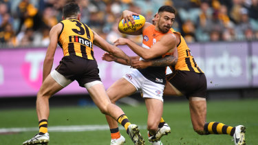 Double teamed: Hawthorn's Ricky Henderson (left and Shaun Burgoyne swoop on Giant Stephen Coniglio.
