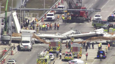 Emergency personnel work at the scene of a collapsed bridge in the Miami area.