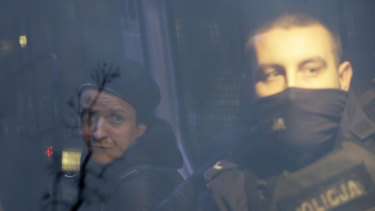Agata Grzybowska, left, a photojournalist, is detained by police in Warsaw, Poland.