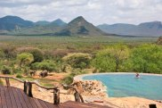 Kenya, A guest enjoying the natural rock swimming pool of Sarara Camp, an ecolodge situated near the Mathews Mountains