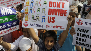 An Indian Muslim boy holds a placard during a protest against Citizenship Amendment Bill.