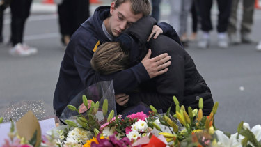 Mourners pay their respects at a makeshift memorial near the Masjid Al Noor mosque in Christchurch. Police on Monday raided properties in Australia in relation to Friday's massacre.