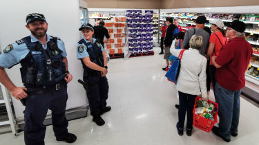 Police officers watch as people queue at a Coles supermarket in Epping, Sydney.