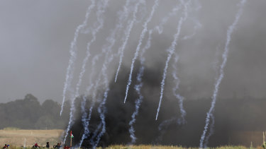 Teargas canisters fired by Israeli troops fall down at Palestinians during the demonstration.