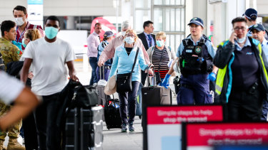 People arriving from overseas were met by police officers at Sydney Airport on Sunday morning.