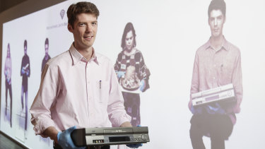 Video preservation specialist Richard Vorobieff shows off an old VCR at a new interactive display area featuring experts with various other exhibits at the National Film and Sound Archive in Canberra.