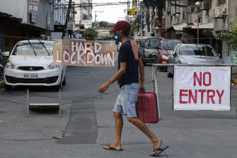 A man passes signs blocking a road during strict community quarantine to prevent the spread of the new coronavirus in Manila.