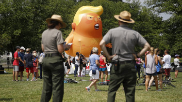 National Park Service rangers view a Baby Trump balloon before Independence Day celebrations. Protesters did not get permission to fly the balloon.
