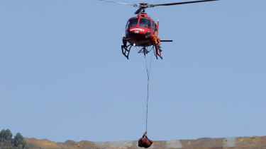 A helicopter lifts a body recovered from the mud five days after the dam's collapse.