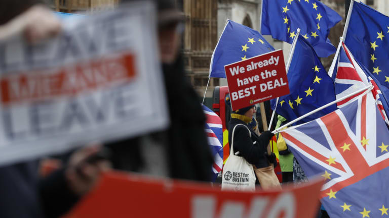 Pro and anti Brexit demonstrators wave their placards and flags outside the Houses of Parliament in London.