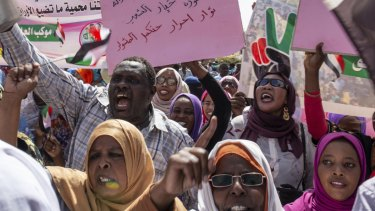 """Protesters carry posters in Arabic that say """"Freedom, justice, and peace, and the revolution is the choice of the people,"""" at the sit-in outside the military headquarters in Khartoum, Sudan."""