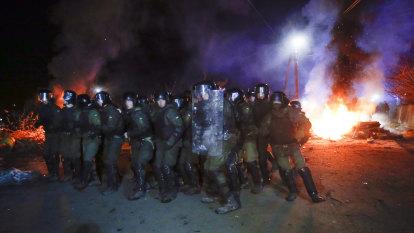 Riot police protect coronavirus evacuees from fearful Ukrainian locals