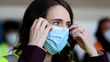 New Zealand Prime Minister Jacinda Ardern adjusts her mask.