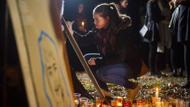 Anna Williams writes a message at the vigil for Eurydice Dixon at Haig Park.