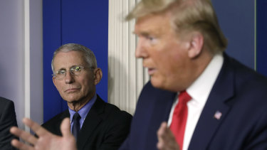 Anthony Fauci, left, listens as President Donald Trump speaks during a Coronavirus Task Force news conference.