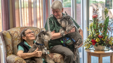 Pastoral carer Kathryn McQuarrie, right, of ACT Companion Dog Club with her mini schnauzers and resident and friend of 58 years Diana Lobb, of St Andrews village in Hughes.