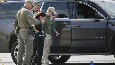 Law enforcement officials process a scene involved in Saturday's shooting.