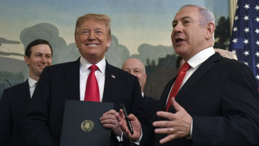 Donald Trump smiles as he holds a proclamation formally recognising Israel's sovereignty over the Golan Heights with Israeli Prime Minister Benjamin Netanyahu.