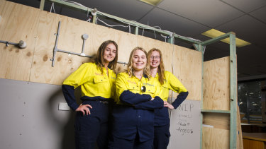 Electrical apprentices Phoebe Thompson, Elina Ulrich and Natalie Fowler in front of a frame they built and wired during training.