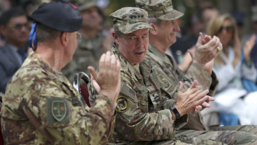 Incoming US Army General Austin Miller, second from left, talks to his colleague as outgoing US Army General John Nicholson, third from left, claps during the change of command ceremony at Resolute Support headquarters, in Kabul, Afghanistan, on Sunday.