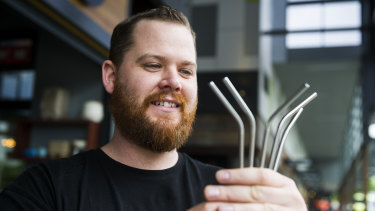 Tristan Morthorpe holding the steel straws at the Atlas cafe in Gungahlin.