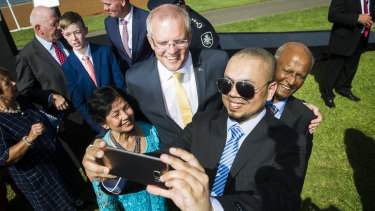 Prime Minister Scott Morrison takes a photo with new Australian citizens Farina Ahmed, Shahzad Ahmed and Iftikhar Ahmed on Saturday morning.
