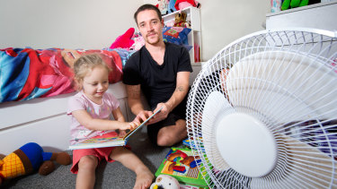 Jay, with his daughter Hayley, 3, in her bedroom, which has the only fan in the house.
