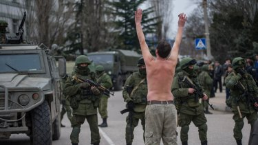 A Ukrainian man stands in protest in front of gunmen in unmarked uniforms on the outskirts of Sevastopol, Ukraine, on March 1, 2014.