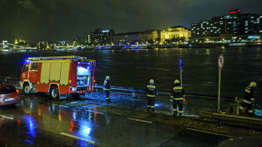 Rescuers search for victims on the river bank early on Thursday.
