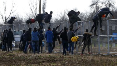Migrants climb a fence installed by Turkish authorities near the Turkish-Greek border in Pazarkule on Wednesday.