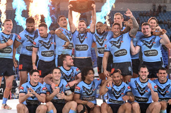 James Tedesco of the Blues holds aloft the Origin trophy after game three on the Gold Coast.