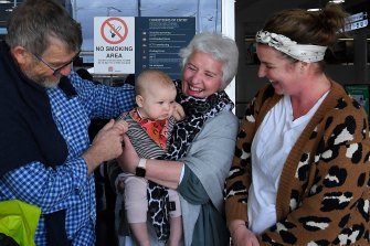Peter Zwart (left) and his wife Anne  (3rd from left) from Christchurch meet their granddaughter Maggie Johnson, five months, and daughter Joanna Zwart (right) at the Sydney International Airport arrivals terminal.