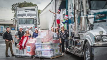 Helpers load the Christmas packages for transport from  Canberra to regional NSW.