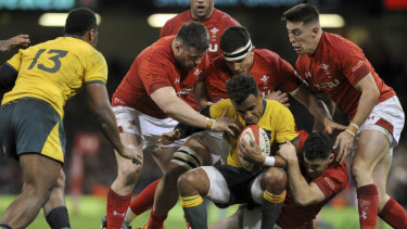 Swamped: Will Genia is tackled by a host of Welsh defenders.