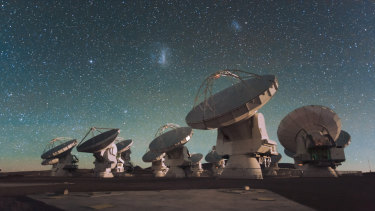 Antennas of the Atacama Large Millimetre/submillimetre Array (ALMA), on the Chajnantor Plateau in the Chilean Andes. The Large and Small Magellanic Clouds, two companion galaxies to our own Milky Way galaxy, can be seen as bright smudges in the night sky, in the centre of the photograph.