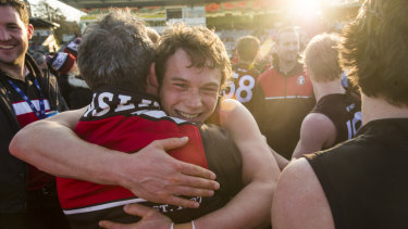 Joshua Taylor hugs Coach Chris Rourke after winning the grand final.