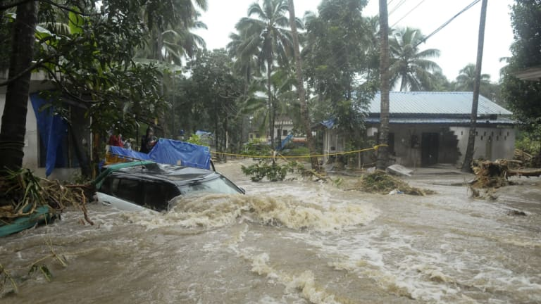 A car is submerged as roads and houses are engulfed in water following heavy rain and landslide in Kozhikode, Kerala state, India.