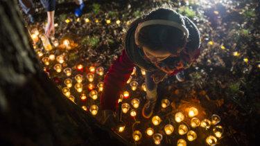 Molly Gifford, 11, writes a message at the vigil for Eurydice Dixon at Haig Park.