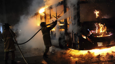 A firefighter extinguishes a burning bus, during a nation-wide education strike in Rio de Janeiro, Brazil.