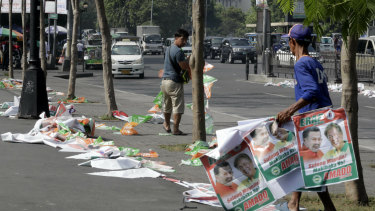 """Manila City public workers remove the campaign posters, mostly that of incumbent mayor and former president Joseph """"Erap"""" Estrada after the vote."""