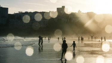 Bathers at Bondi Beach as the sun sets.