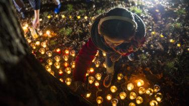 Molly Gifford, 11, writes a message at a vigil for Eurydice Dixon.