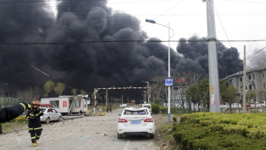 Firefighters walk past the site of a factory explosion in Jiangsu province in eastern China.