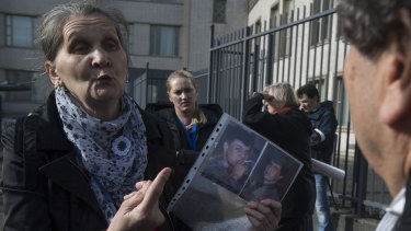 A woman with the Mothers of Srebrenica holds the photographs of two victims of the Bosnian war as she talks to the legal team for Radovan Karadzic, right, after the court upheld his conviction at The Hague, Netherlands.