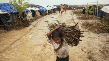 A young boy carries firewood in the rain in Kutupalong camp. Kutupalong camp is the largest settlement in Cox's district. It is estimated that over 100,000 people live inside the camp.