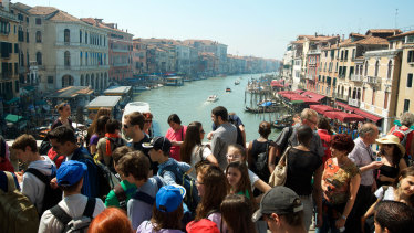 Crowds of tourists pass along the Rialto Bridge against a view of the Grand Canal in Venice.