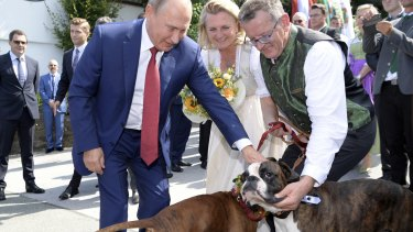 Russian President Vladimir Putin, left, pets dogs as he attends the wedding of Austrian Foreign Minister Karin Kneissl, centre, with with Austrian businessman Wolfgang Meilinger, right, in Gamlitz.