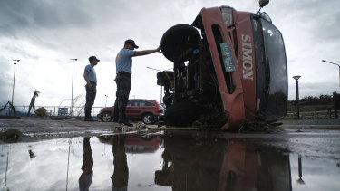 Police inspect a truck that was damaged as Typhoon Kammuri slammed Legazpi city, in south-east Manila.
